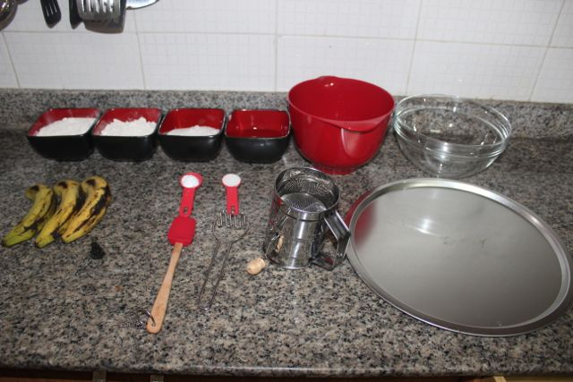Everything we needed.  Ingredients: 3 very ripe bananas, 2 cups of flour, 2/3 cups of sugar, 1/2 cup of vegetable oil, 1 teaspoon of salt and 1 teaspoon of baking soda.  Utensils: 2 bowls, a baking tray/pan, a floor sifter,  a masher, a mixing spoon (a wooden one is more effective) and a spoon (for scooping the batter onto the tray).