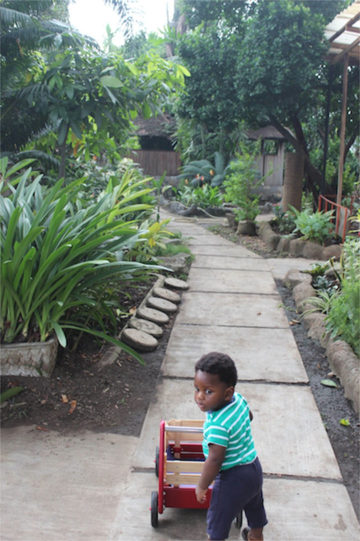 The entrance to the park. It was neat and very green. Plants and flowers along the walkway. He was able to use his wagon on the walk way.