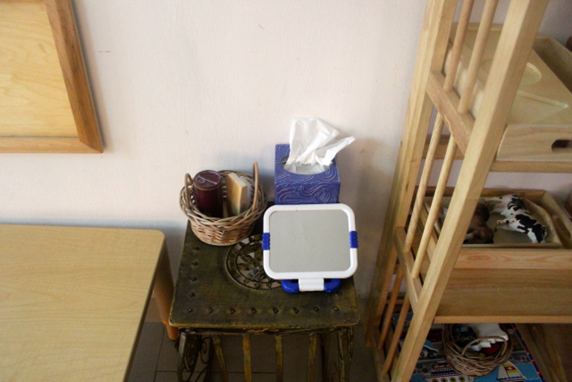 It holds a small basket containing powder and a hair brush, a tissue box and a small mirror