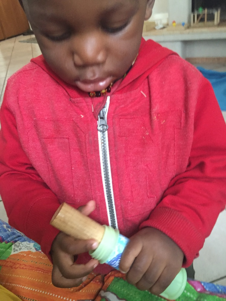 I bought the boys some bubble liquid. Metu mostly spilled his own but as soon as the container was empty, he looked at it and his face lit up and he walked away. I was curious and just watched. He came back with the thick dowel and immediately tried to fit it in. It was like he immediate knew it would fit. We talk about this sensorial impression or muscular memory a lot in Montessori. It is so important for children to work with their hands.